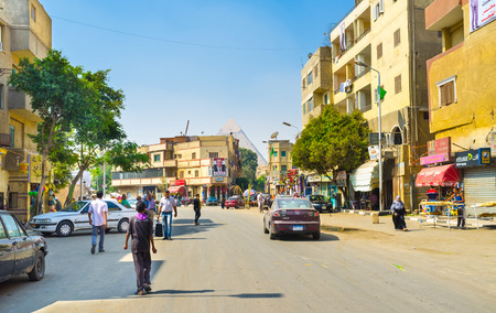 cheops: GIZA, EGYPT - OCTOBER 10, 2014: The residential street in the modern town with the top of the Pyramid behind the houses, on October 10 in Giza.