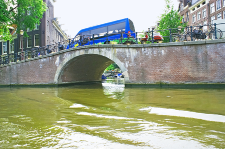 amstel river: Arch bridges are very popular in Amsterdam, besides they are beautiful, The Netherlands. Stock Photo