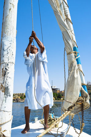 boatman: The boatman sets the sail on the traditional Egyptian boat, named felucca, Aswan, Egypt.