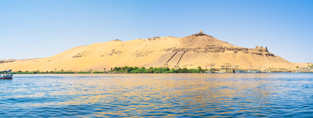 bank western: Panorama of the western bank of Nile river with the famous ancient landmark, Aswan, Egypt.