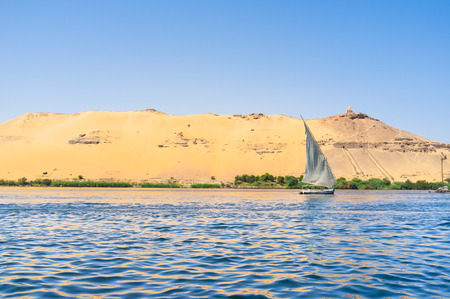 white nile: The white sail of felucca with the rocky Nile bank on the background, Aswan, Egypt.