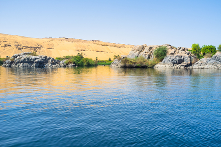 The tiny rocky islets in Nile surrounds the western river bank next to the Elephantine Island, Aswan, Egypt.