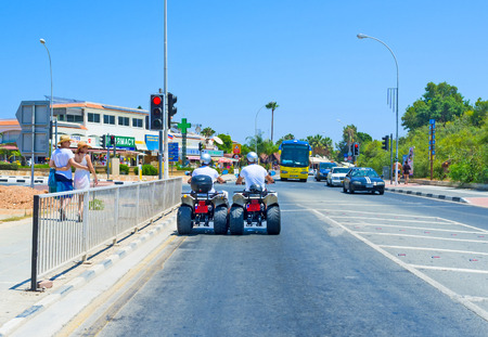 four wheeler: AYIA NAPA, CYPRUS - AUGUST 1, 2014: Two friends talk during the lazy riding on quads, on August 1 in Ayia Napa.