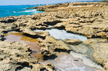 crystallized: The puddles with the crystallized salt among the rocks next to the seashore, Ayia Napa, Cyprus. Stock Photo