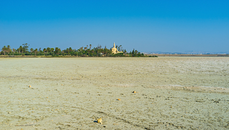 dried up: The dried up Larnaca Salt lake with the ancient mosque on its bank among the lush greenery, Cyprus. Stock Photo