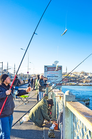 city fish market: ISTANBUL, TURKEY - JANUARY 13, 2015: The lucky fisherman with the fish on the hook on Galata Bridge, on January 13 in Istanbul.
