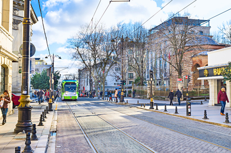 kapalicarsi: ISTANBUL, TURKEY - JANUARY 13, 2015: The tourist street in historic neighborhood with the green tram on the road, on January 13 in Istanbul.