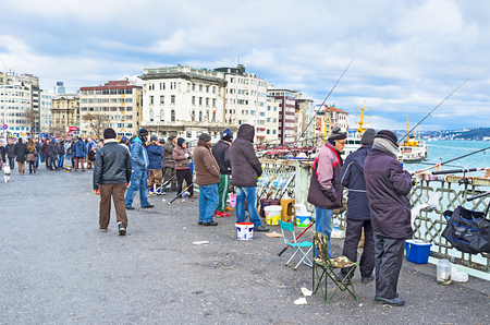 city fish market: ISTANBUL, TURKEY - JANUARY 13, 2015: The local fishermen spend their free time on Galata bridge, enjoying the fishing in the city centre, on January 13 in Istanbul, Turkey.