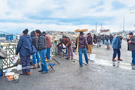 city fish market: ISTANBUL, TURKEY - JANUARY 13, 2015: The dealer walks among the fishermen and carries a tray of bread and buns on his head, on January 13 in Istanbul, Turkey.