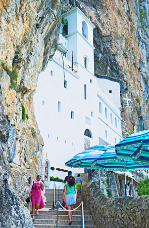 diminutive: NIKSIC, MONTENEGRO - JULY 17, 2014: The white, rock-hewn upper Ostrog Monastery, holds two diminutive cave-churches, on July 17 in Niksic.