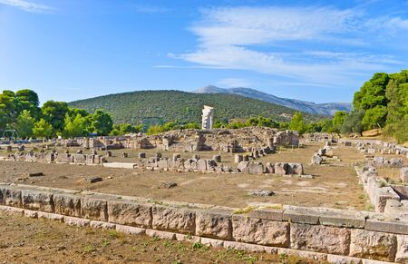 The foundations of the different buildings at the Sanctuary of Asclepius with the scenic mountains on the background, Epidavros, Greece.