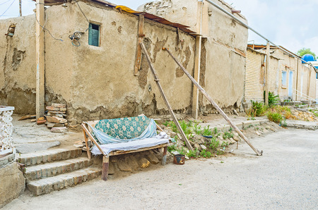 rickety: The homemade bench stands in front of the house with the wooden beams proping up its rickety wall, Bukhara, Uzbekistan.