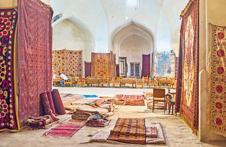 traditional goods: BUKHARA, UZBEKISTAN - APRIL 28, 2015: The tiny cafe in the middle of the trading dome surrounded by the numerous carpets and other traditional goods, on April 28 in Bukhara.