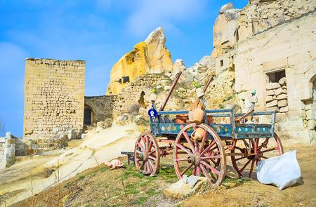 carreta madera: El viejo vagón de madera que cuelga con las vasijas de barro es la publicidad de los puestos de souvenirs pueblo en Cavusin, Cappadocia, Turquía.