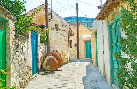The narrow street with the small stone houses, colorful wooden doors and old amphoras, Omodos, Cyprus.