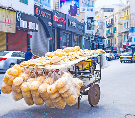nabi: ALEXANDRIA, EGYPT - OCTOBER 11, 2014: The old cart with the flat bread stands in the middle of the shopping street, on October 11 in Alexandria.
