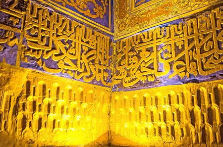 registan: SAMARKAND, UZBEKISTAN - APRIL 30, 2015: The wall of the old mosque in Tilya Kori Madrasah decorated with the persian hieroglyphs made of carved plaster and covered with gilt, on April 30 in Samarkand. Editorial