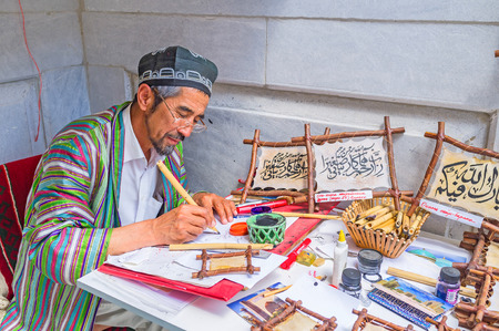 beg: SAMARKAND, UZBEKISTAN - APRIL 30, 2015: The master of calligraphy demonstrates his skills in the art center in the courtyard of Ulugh Beg Madrasah, on April 30 in Samarkand.