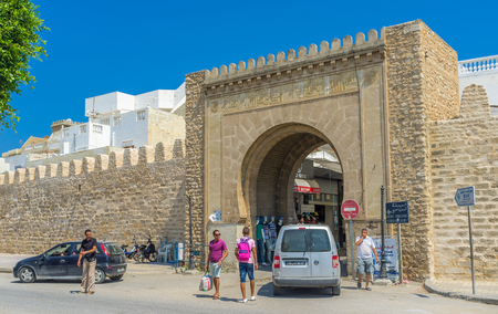 separates: MONASTIR, TUNISIA - AUGUST 29, 2015: The medieval gate separates the modern town from the historic Bab el-Gharbi neighborhood, on August 29 in Monastir.
