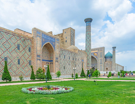 registan: SAMARKAND, UZBEKISTAN - APRIL 30, 2015: The colorful mosaics of the Registan Square complex are well combined with fresh greenery of the garden, on April 30 in Samarkand.