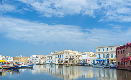 old towns: BIZERTE, TUNISIA - SEPTEMBER 4, 2015: The beautiful reflection of the old towns buildings in calm water of the fishing port, on September 4 in Bizerte.