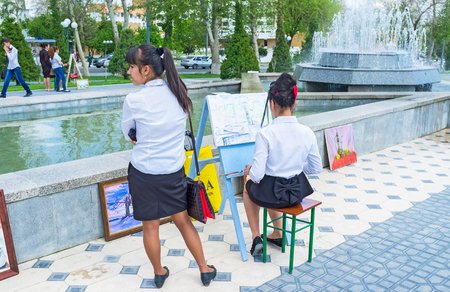 university fountain: SAMARKAND, UZBEKISTAN - MAY 1, 2015: The school girl paints the cityscape during the celebration of the Fountain Day at the University boulevard, on May 1 in Samarkand. Editorial