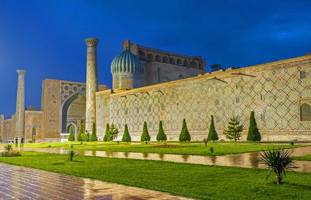 registan: The wet floor tiles reflects the bright illuminated buildings of the Registan Square, Samarkand, Uzbekistan.