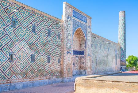 registan: The side wall of Tilya Kori Madrasah with the beautiful portal and ruins of the minaret, Samarkand, Uzbekistan. Stock Photo