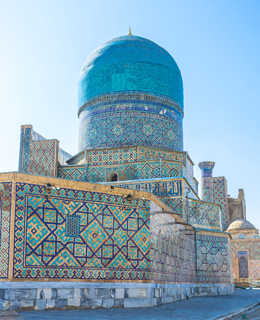 The bright blue dome of Tilya Kori Madrasah goes well with the brick walls, covered with geometric patterns, Samarkand, Uzbekistan.
