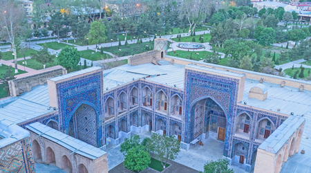 registan: The high minaret of Ulugh Beg Madrasah overlooks its courtyard and the large garden, surrounding the Registan Square, Samarkand, Uzbekistan. Stock Photo