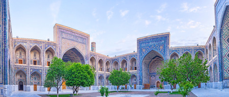 registan: The Uzbek glazed tiles, covering all the Registan Square change their color during the sunrise, Samarkand, Uzbekistan. Stock Photo