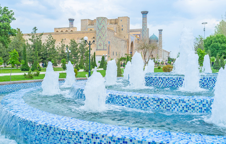 registan: The blue mosaic fountain with the medieval architecture of the Registan Square on the background. Stock Photo