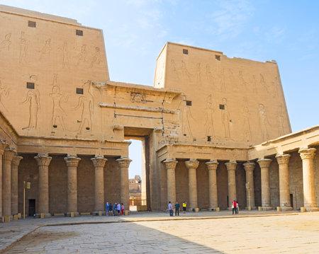horus: Edfu, Egipto - 07 de octubre 2014: El patio del antiguo Templo de Horus con las numerosas columnas de piedra y el portal decorado con antiguos dioses egipcios, el 7 de octubre en Edfu.