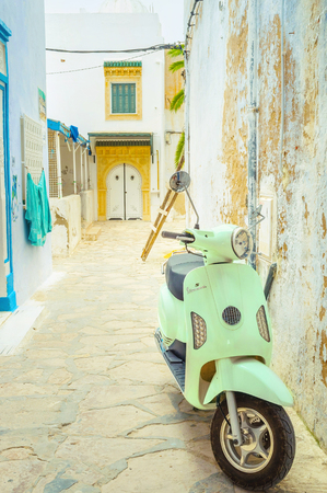 HAMMAMET, TUNISIA - SEPTEMBER 6, 2015: Scooter is the comfortable and maneuver transport in the narrow streets of Medina, on September 6 in Hammamet.