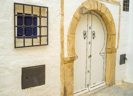 souq: The old stone door frame and wooden door in traditional arabic form, Hammamet, Tunisia.
