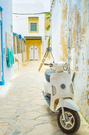 slums: HAMMAMET, TUNISIA - SEPTEMBER 6, 2015: Scooter is the comfortable and maneuver transport in the narrow streets of Medina, on September 6 in Hammamet.