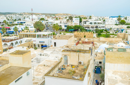souq: HAMMAMET, TUNISIA - SEPTEMBER 6, 2015: The high ramparts of the fortress overlook all the citys white roofs, on September 6 in Hammamet.