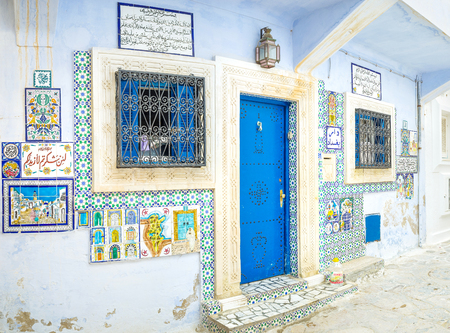 souq: HAMMAMET, TUNISIA - SEPTEMBER 6, 2015: The facade wall of the art gallery decorated with pictures and arabic texts made on glazed tiles, on September 6 in Hammamet.