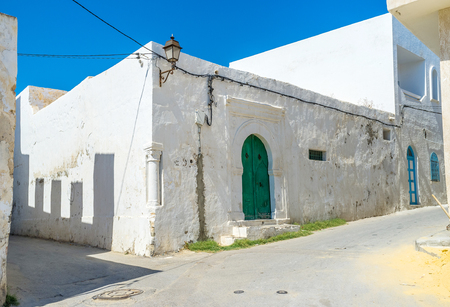 imbedded: The white mud house decorated with small column imbedded in the corner of the house, Mahdia, Tunisia.