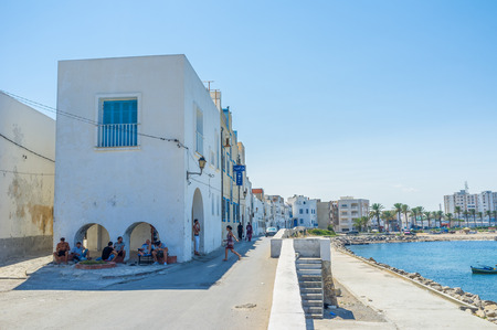 seaside resort: MAHDIA, TUNISIA - AUGUST 29, 2015: The locals hide in the shade of the house on the old promenade, on August 29 in Mahdia