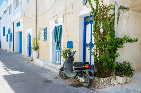 moped: The old moped parked next to the door of residential house, Mahdia, Tunisia.