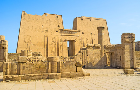 The massive stone portal of the Horus Temple decorated with carved images of the ancient Gods, Edfu, Egypt.