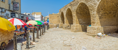 spontaneous: SOUSSE, TUNISIA - AUGUST 28, 2015: The inner side of citadel wall and the colorful sunshades of the merchants of spontaneous market, on August 28 in Sousse.