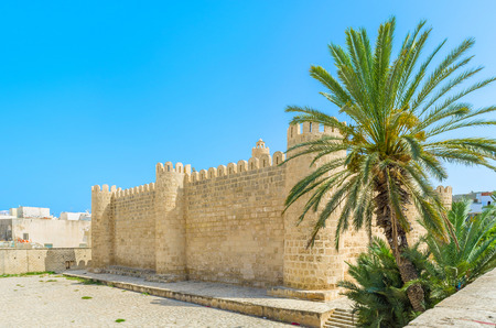 rampart: The huge rampart of the Ribat citadel behind the green palm tree in the center of Medina, Sousse, Tunisia.