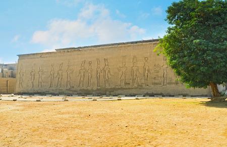 horus: La parte trasera del templo de Horus, con los relieves monumentales y el gran �rbol verde entre el paisaje del desierto, Edfu, Egipto. Foto de archivo