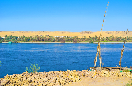 The old felucca on the bank of the Nile river in the Aswan suburb.