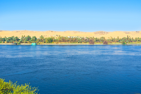 The countryside landscape with the small village on the bank of Nile river, Aswan suburb, Egypt.