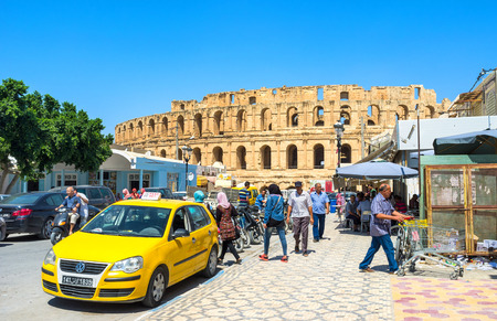 crowded street: EL JEM, TUNISIA - SEPTEMBER 1, 2015: The yellow taxi next to the roman amphitheatre on the crowded street, on September 1, in El Jem. Editorial