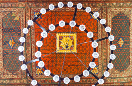 interior architecture: DIYARBAKIR, TURKEY - JANUARY 15, 2015: The ceiling in prayer hall of the Great Mosque with the colorful ornaments and round chandelier, on January 15 in Diyarbakir. Editorial