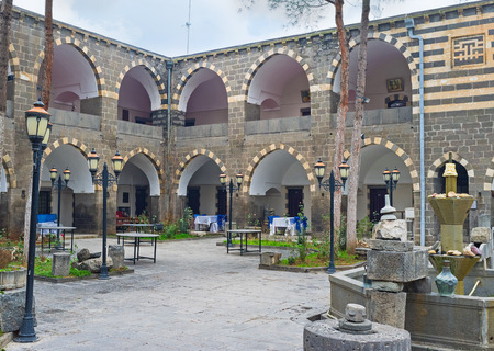 guides: DIYARBAKIR, TURKEY - JANUARY 15, 2015: The  courtyard of Deliller Hani (Guides Khan), that has many rooms and nice outdoor restaurant, on January 15 in Diyarbakir.